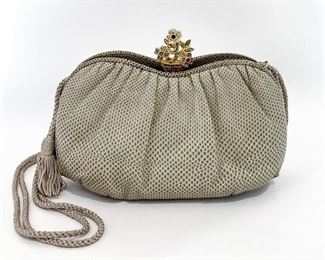 """Judith Leiber stone snake texture leather bean shaped bag with a crystal potted flower closure. Two open pockets are on either side of the center closure pocket. Center opens and expands to reveal a lavender lining with an open and a zipper pocket. Comes with double-sided mirror, tasseled comb, and coin purse. Size is 9"""" length, 6.25"""" height, and 3.75"""" depth. Braided and doubled lavender strap is 36"""" long and has tassels on the end. Leather is darker at the bottom seams. Condition is very good with minimal signs of wear on lining. $395"""