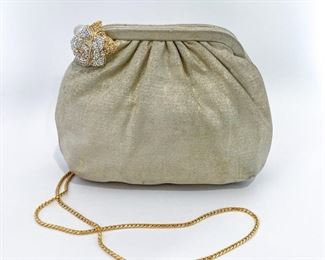 """Judith Leiber metallic gold and cream textured bag with rhinestone rose and pearl clasp. Clam shell mouth opens to reveal a silky cream lining. Features an open pocket and a zipper pocket. Comes with double-sided mirror, tasseled comb, and coin purse. Size is 8.25"""" length, 6"""" height, and 3.5"""" depth. Braided gold metal strap is 40"""" long. Condition is excellent with minimal sign of wear inside. $295"""