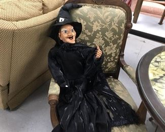 A ghoulish witch seated in a wonderful reproduction arm chair