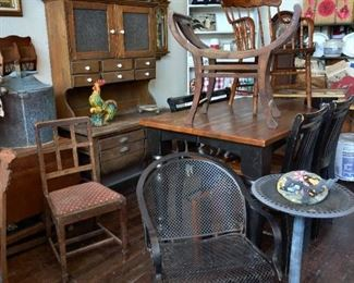 Primitive hoosier-needs some love. to the left of hoosier is a barley twist gate leg table with a copper still on top. Newer black base table with four chairs.