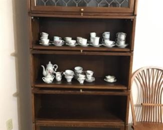 Barrister bookcase, inside a collection of demitasse cups and saucers.