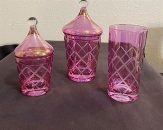 Beautiful pink glass vanity set in mint condition. No markings and not sure of the age but at least 60 years old. (3) pieces that are cut glass, two have the lids and one heavy drinking glass. $30