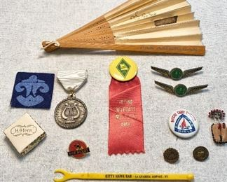 "Top-Pan American airlines fan, Middle row-2 ""Ozark Airlines"" wing pins, Farm Bureau ""1949"" voting delegate ribbon/pin, 1987-88 Friendship Circle music medallion. Bottom row-H.Stern box, Camp Fire Girls pin, Moe Bandy pinback, Cub Scouts Bobcat pin, old Presbyterian SS pinback, beaded Indian moccasin pin, airport bar stirrer ""Kitty Hawk Bar, La Guardia Airport, NY. (Lot of 13) $20"