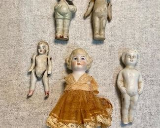 Old porcelain bisque dolls, two with jointed arms. Dollhouse doll with dress has no arms or legs, doll on far right has one foot chipped. All others are good and very old. (Lot of 5) $24