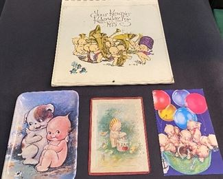 "Kewpie items-""1975"" Calendar, kewpie dish, old framed Kewpie postcard, Kewpie postcard ""1990's"" unused. $12"