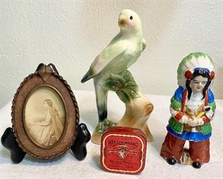 "Group of collectibles - Ceramic parrot with great color, measures 8"" tall, very old leather & copper frame with lady picture, ribbon tin ""Keelox"", and ceramic Indian statue, measures 6"" tall, marked on bottom ""Made in Occuipied Japan."" (Lot of 4)  $24"