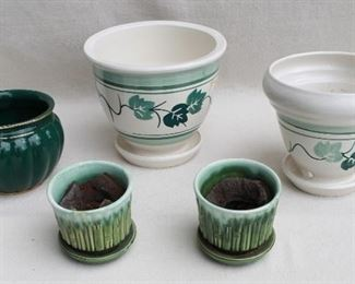 """$10 each Upper center: Glazed painted ceramic, ivy motif, attached drip tray.  H: 8""""   diameter: 9"""" $20 each Lower center: Set of 2 green glazed ceramic, bamboo motif, attached drip tray, signed McCoy USA 0372.  H: 4""""   diameter: 4.5"""" $10 each Right: Glazed painted ceramic, ivy motif, attached drip tray.  H: 7.5""""   diameter: 8"""" $20 Left: Dark green glazed ceramic w/ gold trim.  Signed (see detail). H: 5""""   diameter: 7"""" [Props]"""