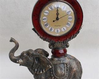 """$95 Cast resin African elephant supporting an ornate clock w/ Roman numerals & 3 hands; appears as cast metal & burgundy enamel.  L: 9.5""""   H: 16""""   D: 4.5""""   clock face diameter: 4"""" [Props]"""