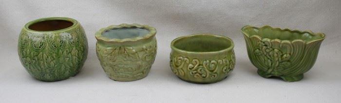 "$20 each Left: Green round ceramic cachepôt, embossed Arts & Crafts sunflower decoration.  H: 5.5""   diameter: 7""  Left center: Green round ceramic cachepôt, fluted rim.  H: 4.5""   diameter: 6""  Right center: Green round ceramic cachepôt.  H: 3.5""      diameter: 6""   Right: Green boat-shaped ceramic vase.  L: 8""   W: 4.5""   H: 4.5"" [Props]"