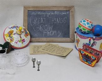 """Lot of children's toys: New painted tin drum w/ carrying cord (H: 4.5""""   diameter: 8"""");   new painted tin plunger top (H: 7.5""""   diameter: 7"""");  vintage wooden top (AS IS string missing)(H: 4.5""""   diameter: 3"""");  new toy accordion, brightly colored (L: 5""""   W: 3.5""""   D: 1.5"""");  blackboard, $20 blackboard, slate w/ unfinished wood frame (L: 14""""   W: 10""""   D: 0.5"""");  2  calligraphy books, paperback (L: 7.5""""   W: 5"""");  doll's tea set of plastic pressed glass (10 pieces);  2 colorful rubber balls (diameter:  3.5""""and 3""""). [Bin 32]"""