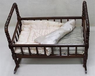 "$45 Vintage doll's cradle of dark wood w/ turned spindles, slat bottom, blue-striped mattress, pale pink satin comforter.  L: 22""   W: 13""   H: 17.5""   rockers: 19"" [Bin 32b]"