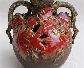"$60 - Brown/green ceramic round vase, pierced design of red fall leaves, 2 handles.  W: 7.5""   H: 8""   D: 6"" [Vase]"