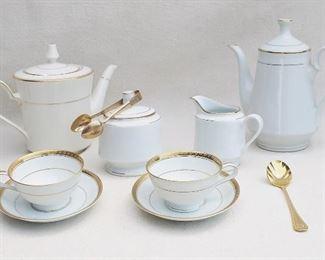 """$40 - LOT Noritake Richmond pattern: - White porcelain teapot w/ gold trim.  W: 10""""   H: 8""""   D: 5.5"""" -White porcelain coffee pot w/ gold trim.  W: 8.5""""   H: 9""""   D: 5""""  - White porcelain creamer w/ gold trim.  L: 5""""   W: 3""""   H: 4"""" - White porcelain sugar bowl w/ gold trim            H: 5""""      diameter: 4""""      Made in China    - 2 white porcelain cups & saucers w/ gold trim.  H: 2.5""""    saucer diameter: 6"""" - Brass sugar spoon.  L: 6.5""""   W: 1.5"""" - Brass sugar tongs.  L: 5"""" [Bin 18]"""