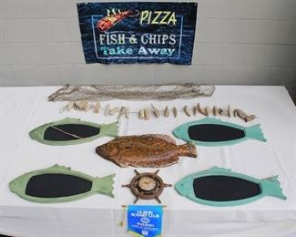 """$60 - LOT of nautical set dressing: hanging green wooden fish w/ chalk board bodies (4); hanging painted wooden fish (1); ship's wheel battery clock (1); nets (5); strings of driftwood floats (2); Dublin Rotary Club banner (1); plastic banner """"Pizza Fish & Chips Take Away"""" (1)  [Bin 6]"""
