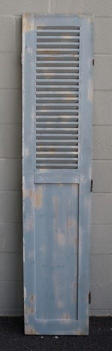 """$75 - Wood shutter, grey distressed finish, stationary louvers on upper half, 3 brass hinges each side, slides on bottom.  W: 16""""   H: 75""""   D: 1"""" [Props]"""