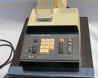"""Vintage cash register, yellow and black, electronic , B&E.  W: 12.5""""   H: 11""""   D: 17""""  AS IS: Minor damage to plastic cover  [Props]"""