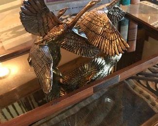 Brass ducks in flight