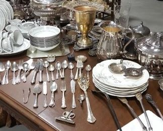 Lots of silver plate and china on antique tables