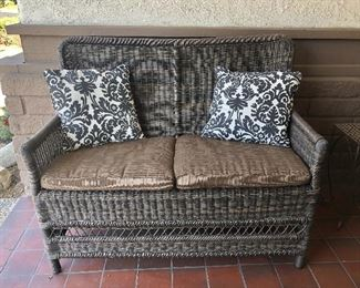 """Lot #4. Price $125. Wicker Patio Loveseat w/ Cushions and Pillows. Made of PVC material.  Excellent condition except a couple of stains on cushions. Dimensions: 45.5""""W x 25""""D."""
