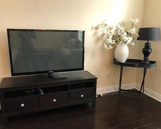 Another TV and TV Stand shown with accent table and décor