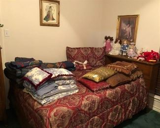 Double bed, comforters, pillows, dolls