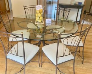 Lot 4050. $1,200.00.  Gorgeous, Italian made glass top dining table on wrought iron pedestal base with brass accent leaf design. there are also 6 wrought iron dining chairs with upholstered seats.  Perfect condition
