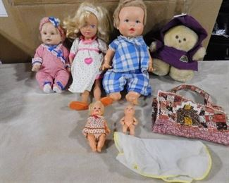 lot of children's baby dolls and a teddy bear