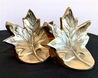 """$30. Pair of brass Maple leaf bookends. Measures 5"""" tall."""