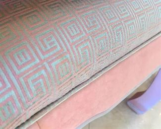 Teal and pink fabric upholstered on the benches beneath the console table.