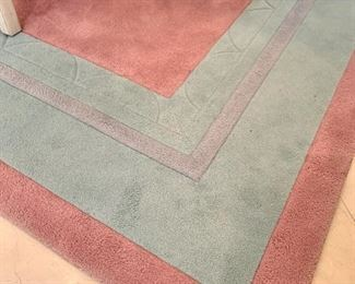 Close up of the pink and teal area rug.