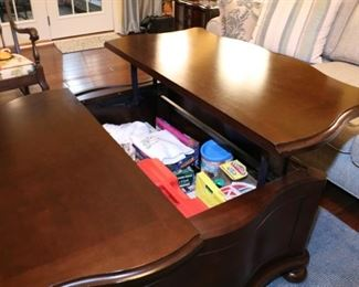 Coffee table top raises up to make a tray table. It also has storage below and drawers in the front.