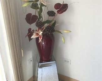 Mirrored stand and floral arrangement in vase