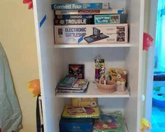 Utility shelf filled with games, crayons, art supplies and morr