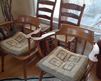Pair of captain's chairs in foreground; ladderbacks in background