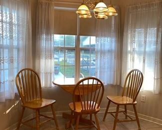 Breakfast table with three chairs. One chair is slightly mismatched.