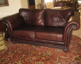 Rolled Arm Leather Loveseat with Wooden Base Plus Nail Head Trim