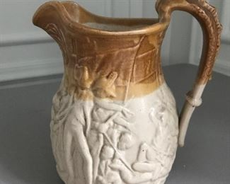"Glazed stoneware pitcher with horn form handle and battle scene in relief, 7"" H x 6.5"" W 