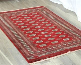Deep red patterned rug with slight fringe accent