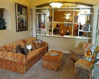 Nice orange sofa with ottoman, original oil painting, occasional tables, custom upholstered chairs, and decor.
