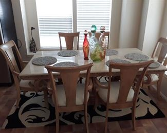 Light  colored wood dining room table with 6 arm chairs.