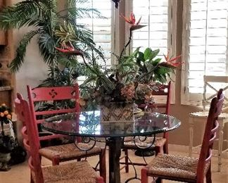 Heavy duty round glass dining table top. Can also be used outdoors. It has a metal base. 4 red chairs.