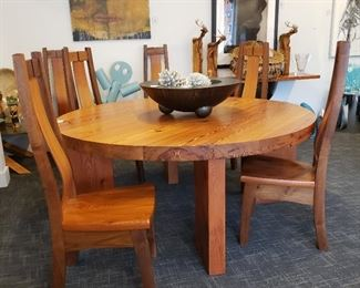 Handcrafted in Taos New Mexico,  solid wood table and six chairs the table is 72 inch round 30 inches tall and 3 inches thick held together with iron rods the chairs are sculpted to fit your back. Wonderful set