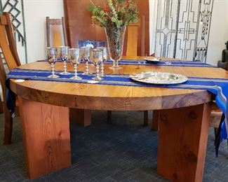 Handcrafted solid wood table and six chairs the table is 72 inch round 30 inches tall and 3 inches thick held together with iron rods the chairs are sculpted to fit your back. Wonderful set