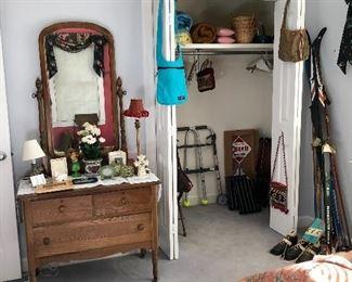 Vintage oak dresser, vintage snow skis, walker. In the closet are wood TV trays