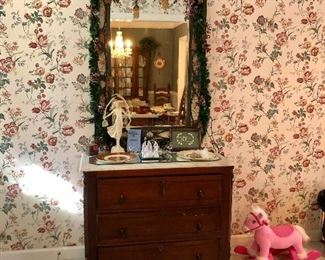 Walnut, marble top 3 drawer chest, a green mirror with Christmas lights and a pink pony.