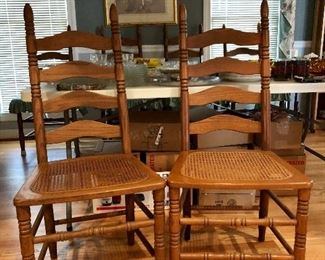 2 of 10 ladder back chairs, oak with cane seats.