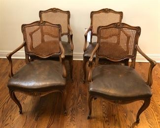 Set of 4 cane and leather dining chairs. Leather and caning is in good as found condition.  Arm on one chair is broken. Other arms are loose. We have restoration resources