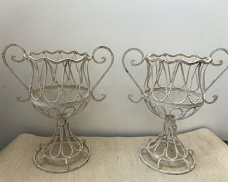 "Two metal planters. Each stands 23"" tall.  Diameter of opening is 12"""