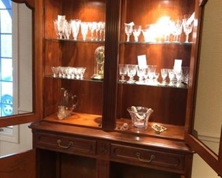 "Stickley china cabinet with interior lighting measures 53"" W x 88"" H x 19"" D. Waterford Lismore crystal, Vannes glass bowl, Bulova clock in cloche, vintage Fostoria etched crystal wine glasses"