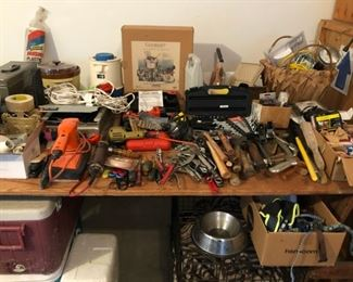 Assorted tools including wrench set, power drill miter saw, Black & Decker Jig Saw, paint brushes and rollers, plumbing wrench, hammer, mallet, belt sander, drill, hack saw, hedge trimmer, spade, ax, pitch fork, sprinklers